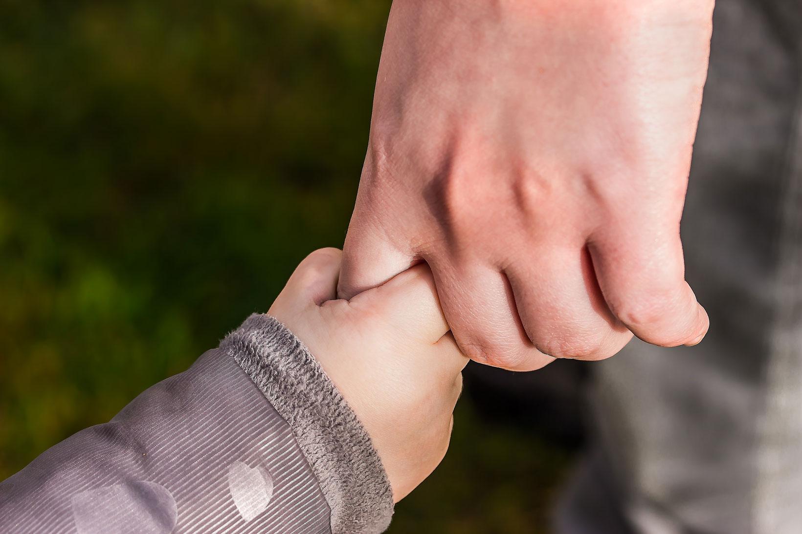 Kinderhand hält sich am Zeigefinger einer Erwachsenenhand fest